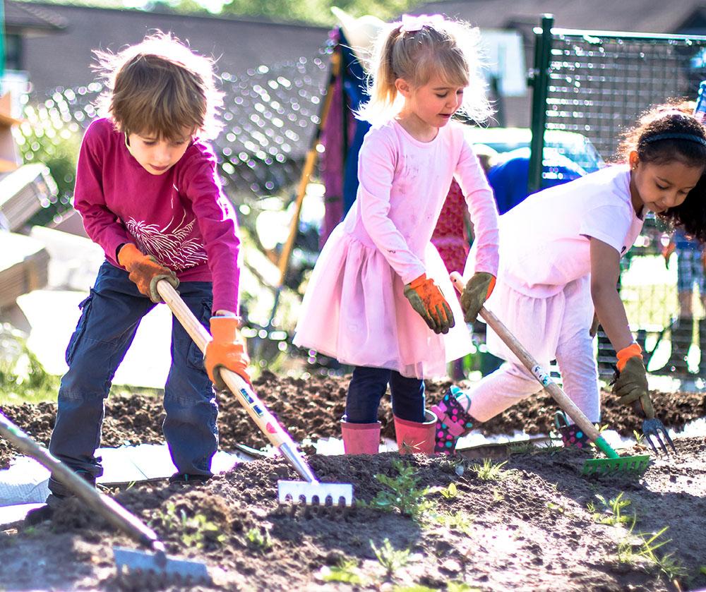 Children with rakes in the garden