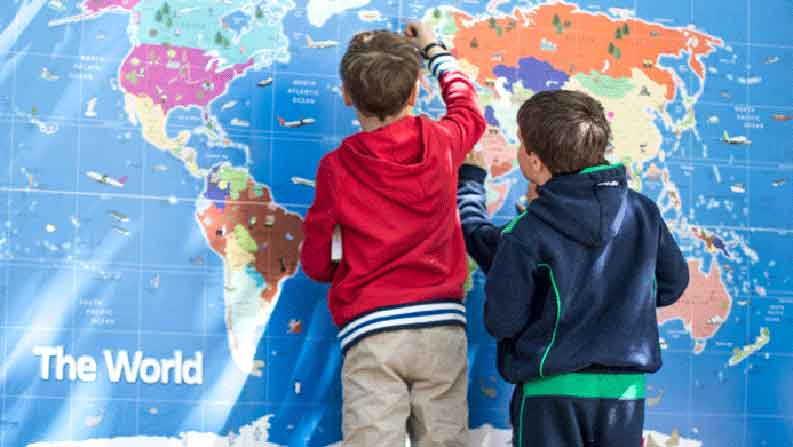 Boys looking at a world map